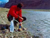 Guy Filtering water from a river