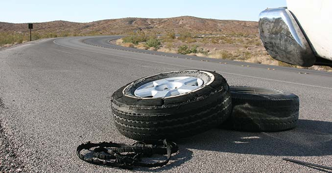 A flat Tire on the side of the Road