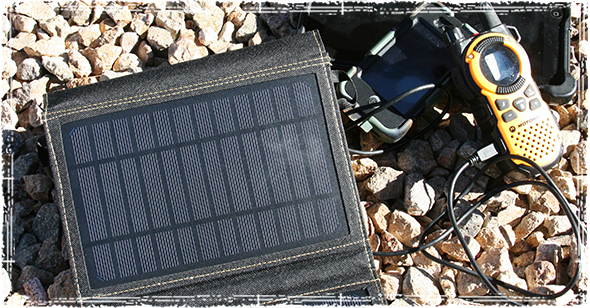SunJack Solar Panel charging an iPhone and a Motorola Radio