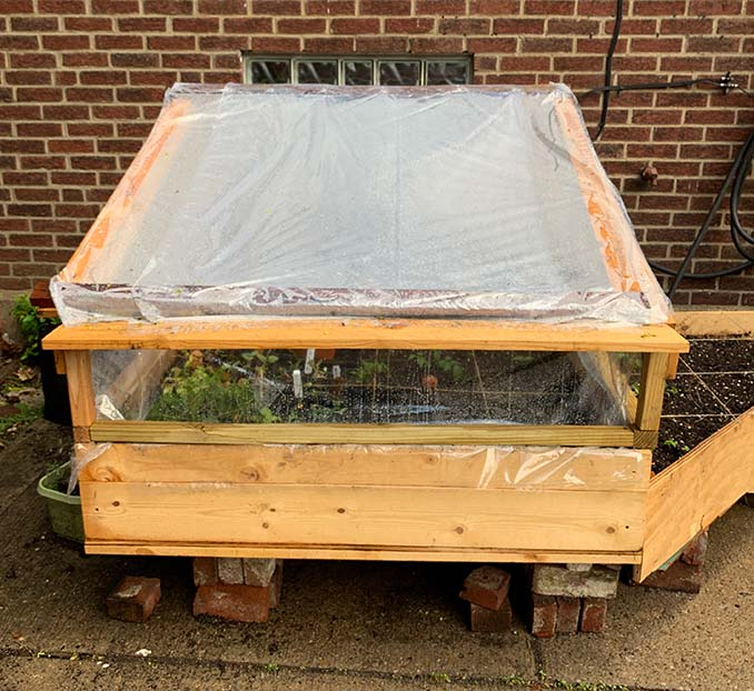 A raised cold frame built with wood and plastic